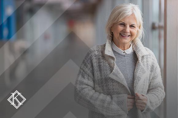 """Mulher em corredor sorrindo. A imagem ilustra a publicação """"Evitar taxa de I.R. para aposentados no exterior, é possível?"""", da Koetz Advocacia."""