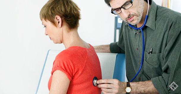 Médico com estetoscópio ouvindo os pulmões de uma paciente. Representa as perícias médicas para obtenção de auxílio doença.
