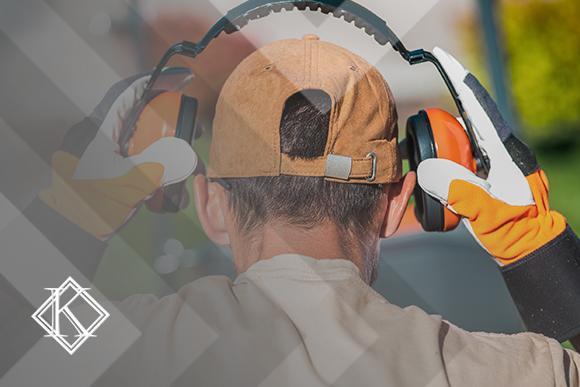 Homem colocando protetores de ouvido para realizar trabalho com ruídos altos. A imagem ilustra a publicação