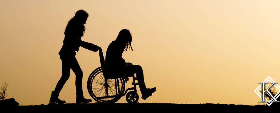 Silhueta de duas mulheres. Uma delas cadeirante e a outra empurrando a cadeira de rodas. Veja aqui informações a respeito da aposentadoria por invalidez.