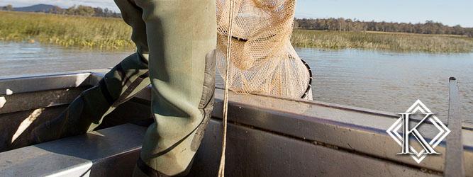 homem dentro de barco removendo materiais da água
