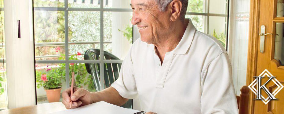 idoso sorrindo e escrevendo em folha de papel