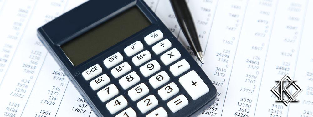 calculadora e caneta em cima de planilha