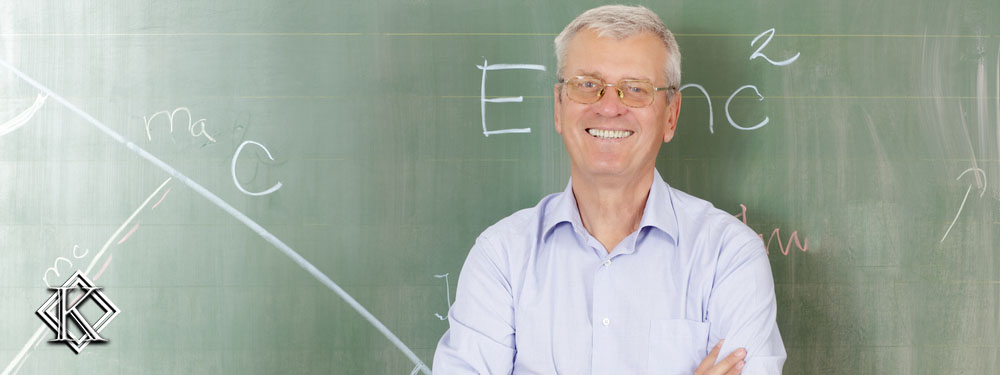 Professor sorrindo de braços cruzados em frente a quadro negro