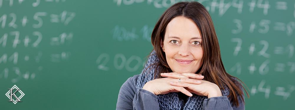 Professora sorridente em frente a quadro negro. Confira informações a respeito da aposentadoria do professor municipal.