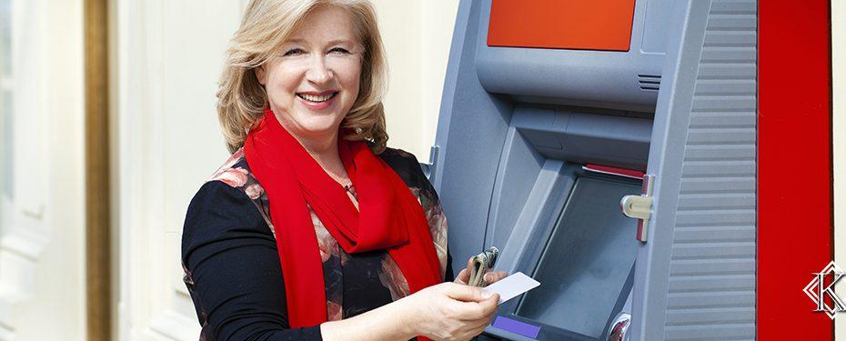 Senhora sorrindo e recebendo pagamento em caixa eletrônico