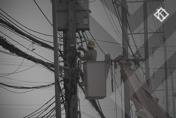 A imagem mostra um trabalhador realizando a manutenção de um poste de luz, elevado por uma grua. A imagem ilustra a publicação