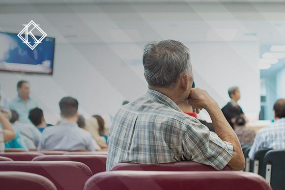 Homem fotografado pelas costas esperando sentado em uma fila de senhas. A imagem ilustra a publicação