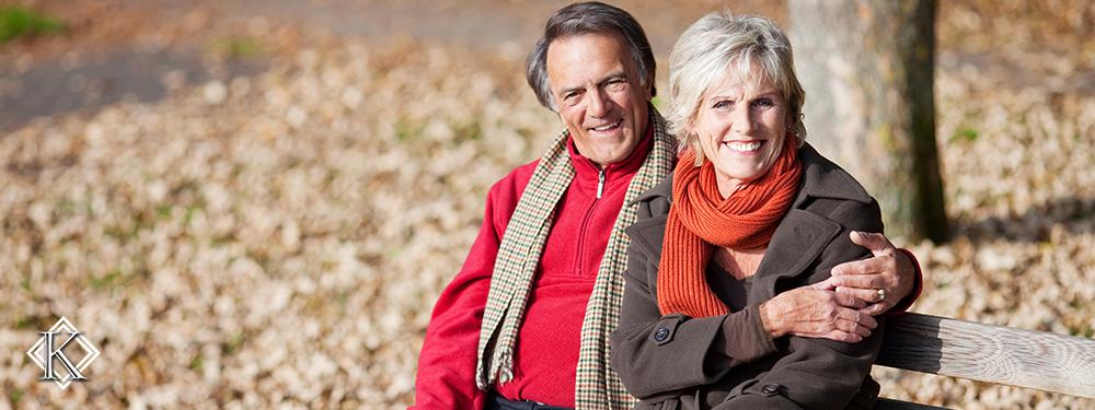 Casal de aposentados sentados em banco de parque