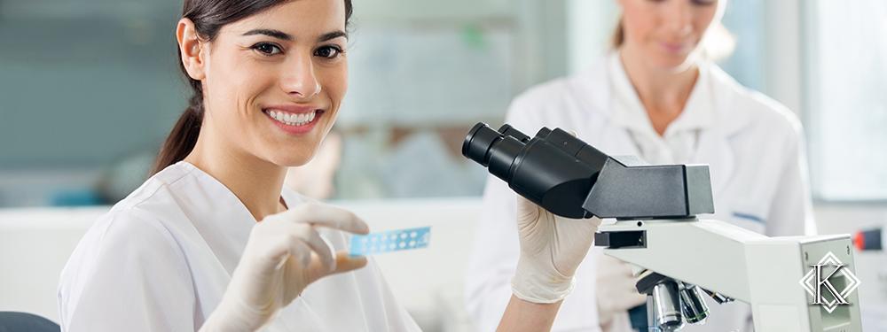 Laboratorista em laboratório em frente a microscópio. Conheça mais sobre a Aposentadoria Especial para Técnico de Laboratório.