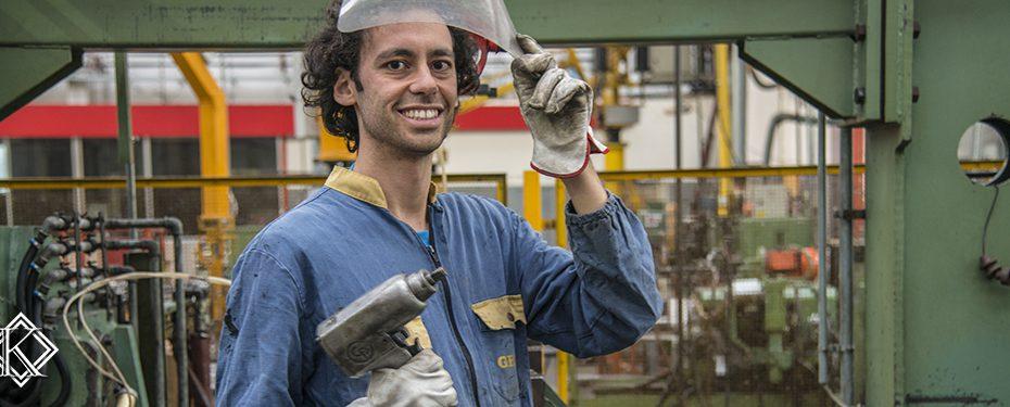 Metalúrgico sorridente levantando proteção dos olhos e com ferramenta na mão. Confira aqui informações sobre a aposentadoria do metalúrgico para entender melhor como funciona o benefício.