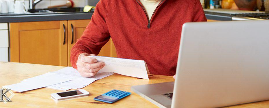 Homem segurando documento sentado em frente ao computador
