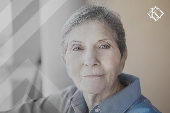 """Mulher de idade avançada sorrindo. A imagem ilustra a publicação """"Cobrança de 25% de aposentados no exterior parada pela Justiça"""", da Koetz Advocacia."""
