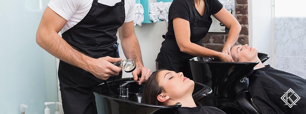 Dois esteticistas lavando cabelos de clientes em salão de beleza. Saiba mais sobre a aposentadoria para autônomo.