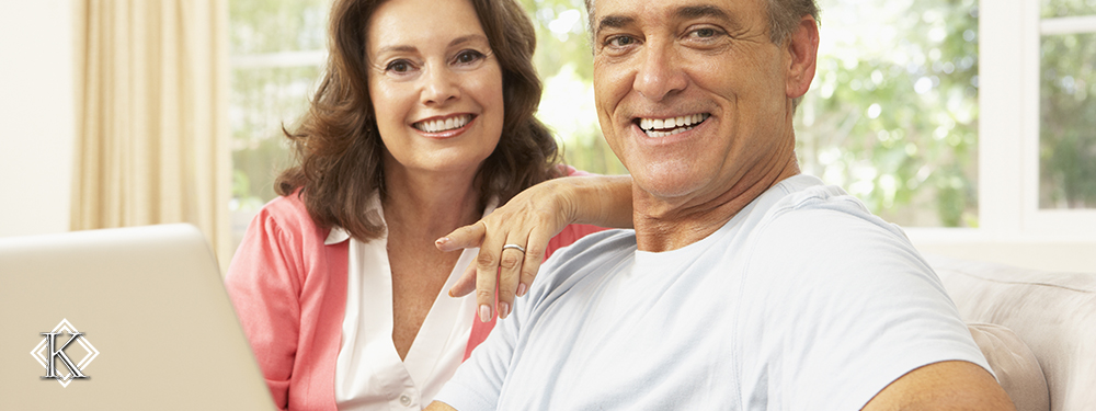 Senhora e senhor sorrindo sentados em sofá em frente à notebook