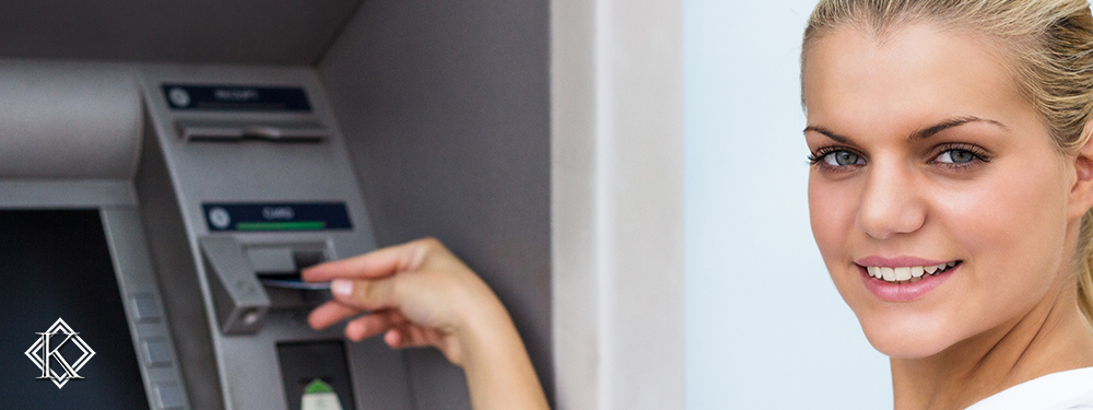 Mulher inserindo cartão magnético em caixa eletrônico