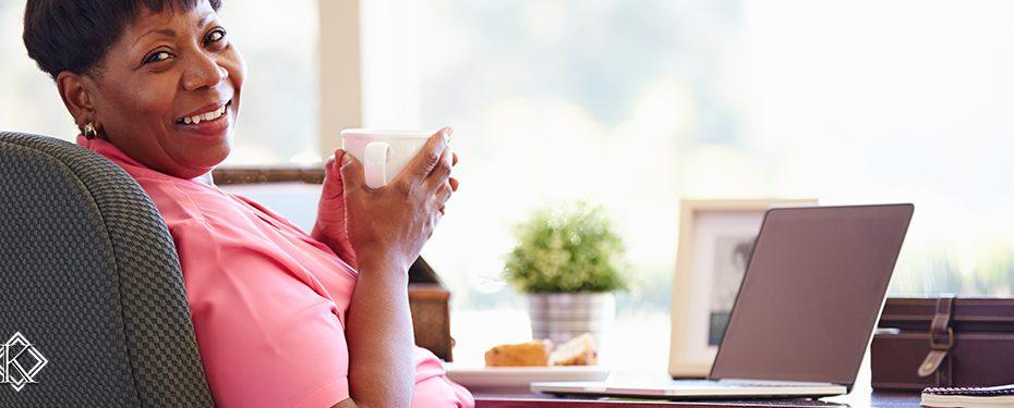 Senhora sorridente tomando café em frente a um notebook