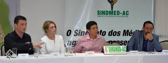 Quatro profissionais lado a lado em uma mesa falando ao público em evento