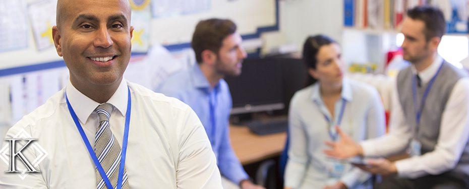 Homem sorrindo com equipe de trabalho em reunião ao fundo