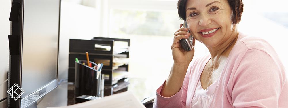 Senhora sorridente ao telefone em frente a um computador
