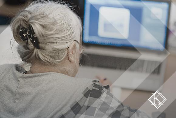 A imagem mostra uma mulher de costas utilizando o computador. A imagem ilustra a publicação