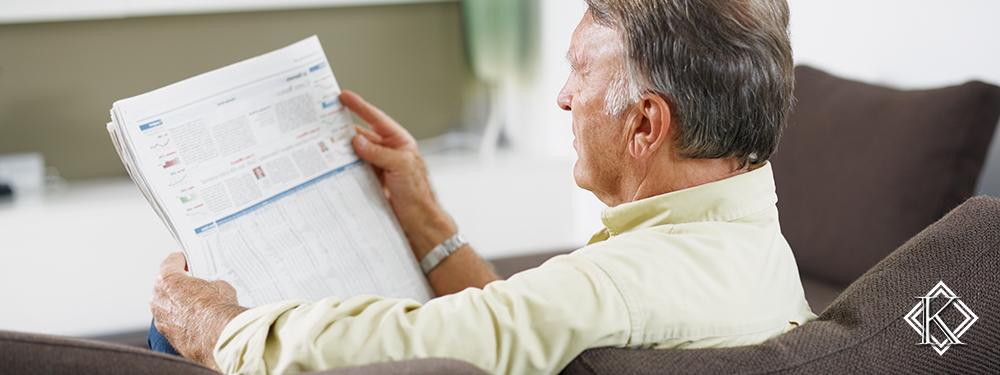 Senhor sentado em sofá lendo jornal