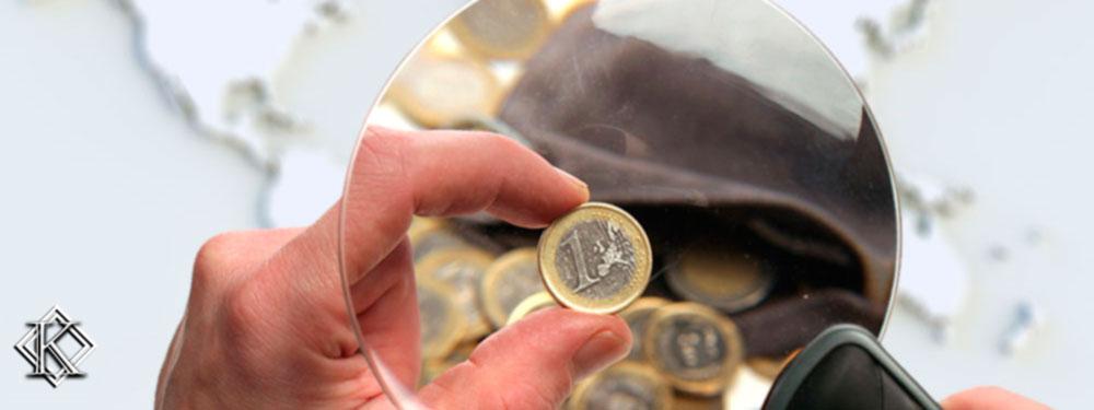 Um mão segurando uma lente de aumento verificando algumas moedas com um mapa de fundo, simbolizando as cobranças indevidas de aposentados no exterior