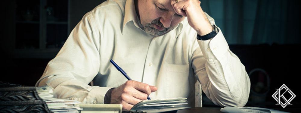 Um homem aflito riscando alguns documentos com caneta e pensando, simbolizando a complementação negada para seu pedido de aposentadoria