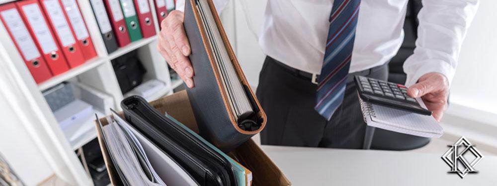 Homem colocando materiais de escritório em caixa de papelão, representando a rescisão de contrato de trabalho de Empregado Público