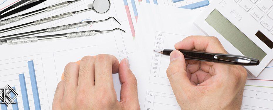 Mão segurando caneta e prestes a escrever em folhas em branco de relatórios e calendários. Há também uma calculadora e alguns intrumentos de dentista sobre os papéis, simbolizando o planejamento da Aposentadoria do Dentista.
