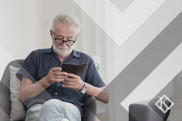 """A imagem mostra um homem concentrado lendo algo em seu Smartphone. A imagem ilustra a publicação """"Complementação da aposentadoria negada pela prefeitura: o que fazer?"""", da Koetz Advocacia."""