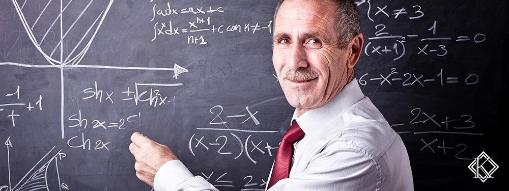 Professor de aproximadamente 50 anos de idade sorridno em frente a um quadro, representando o melhor benefício para aposentadoria de professor.