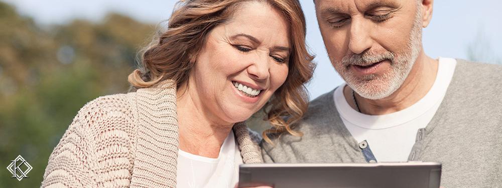 Casal prestes a se aposentar sorrindo e olhando na tela de um tablet, representando a facilidade de consultar a situação do benefício previdenciário pela internet.