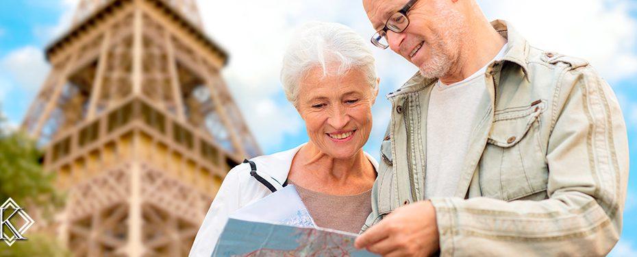 Casal de aposentados verificando um mapa em frente à Torre Eiffel em Paris, representando a aposentadoria no Brasil de quem mora no exterior.