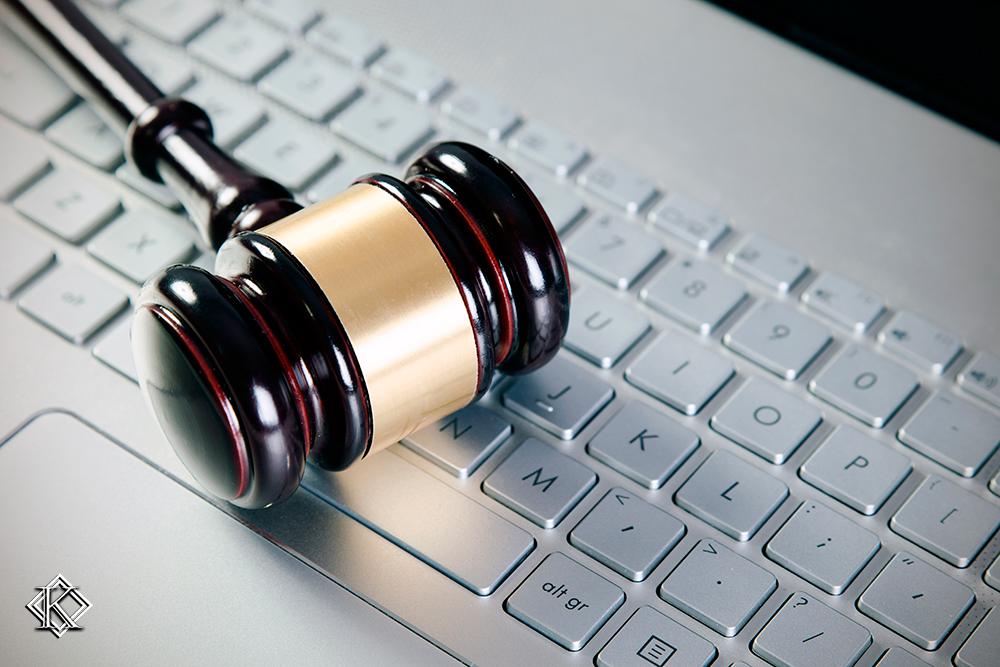 Martelo de juiz sobre teclado de computador ilustrando o texto Advogado Previdenciário - 4 Casos de Contratação Online.