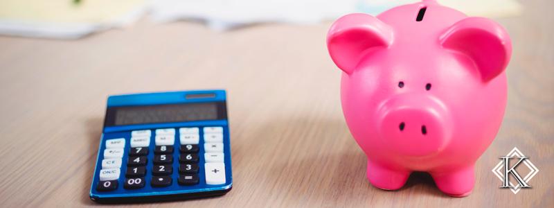 """Calculadora e cofre de porco ilustrando o texto """"Como calcular a aposentadoria: Quanto você vai ganhar?"""""""