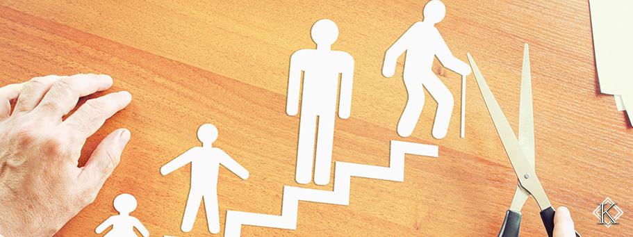 Duas mãos repousadas sobre uma mesa de madeira. Uma delas segura uma tesoura. Sobre a mesa e entre as mãos, um recorte em papel forma a imagem de uma escada e, em cada degrau, diferentes fases da vida, começando por um bebê, passando para uma criança, depois um adulto e, por último, um idoso com uma bengala. O recorte representa as etapas da vida até a idade para se aposentar.