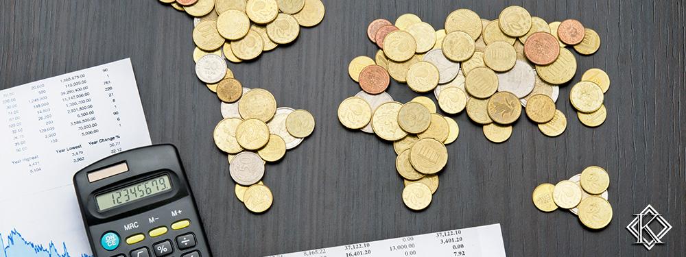 Uma mesa com várias moedas desenhndo os continentes do mundo, alguns papéis com números impressos e uma calculadora. A imagem ilustra as taxas que são aplicadas no valor da aposentadoria dos brasileiros que moram no exterior.