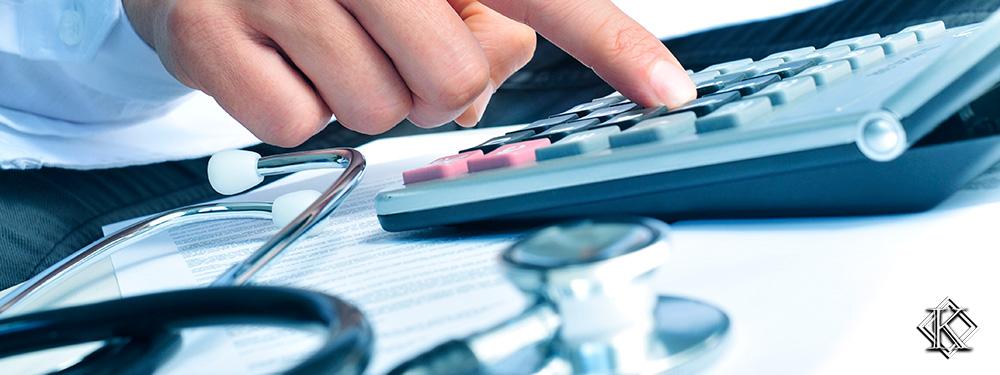 Uma mão calculando números em uma calculardora com um estetoscópio ao lado, representando a complementação de aposentadoria de servidor público da área da saúde.