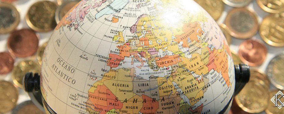 Globo com mapa mundi sobre diversas moedas de países diferentes, representando a incidência dos 25% de retenção do Imposto de Renda sobre os benefícios previdenciários do brasileiro no exterior.