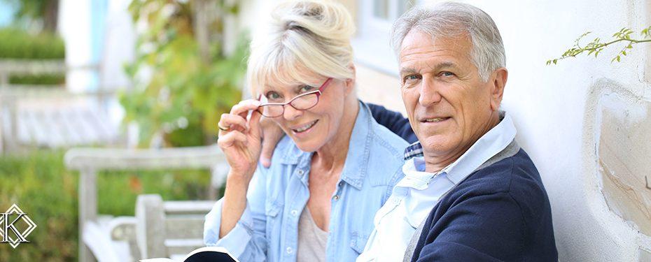 Casal de aposentados lendo livro em varanda. Imagem representa dois aposentados que pensam em voltar a trabalhar para aumentar o valor da aposentadoria.