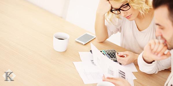 Um homem e uma mulhe jovens sentados à mesa tomando café e calculando valor da aposentadoria com auxílio de uma calculadora, caneta e papéis.