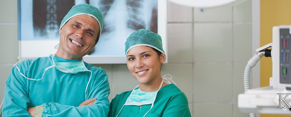 Médico e médica sorridentes em frente à exames de raio x, representando a possibilidade de continuar trabalhando mesmo após a obtenção da aposentadoria especial.