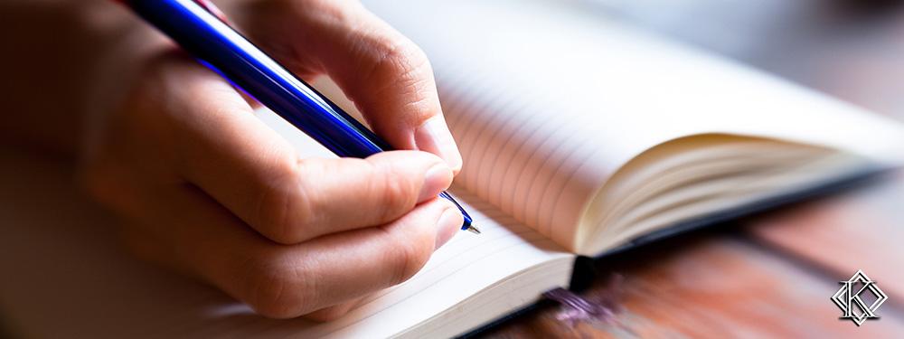 Uma mão anotando algo com uma caneta em um caderno. A imagem representa a atenção que é necessária ter em alguns fatores antes de entrar com o pedido de aposentadoria.