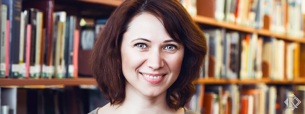 Jovem professora sorrindo em frente à estante com diversos livros. A imagem foi escolhida para representar a importância de se antecipar e realizar o planejamento de aposentadoria de professor.