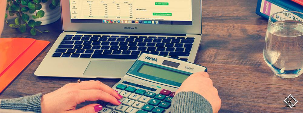 Uma mulher sentada a uma mesa com uma calculadora e um notebook montando uma planilha, representando a importância de fazer um planejamento financeiro e um planejamento de aposentadoria