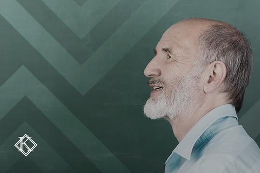"""Retrato em perfil de professor, em frente ao quadro verde. A imagem ilustra a publicação """"Aposentadoria de professor concursado sem previdência própria""""."""