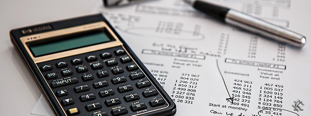 Uma calculadora sobre uma planilha com diversos números impressos e uma caneta que rabiscou alguns deles. Foto representa as diferentes regras para aposentadoria.