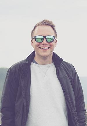 Homem sorrindo de óculos espelhado, jaqueta e moletom sem capuz. Ilustrando uma persona para marketing de conteúdo na advocacia.
