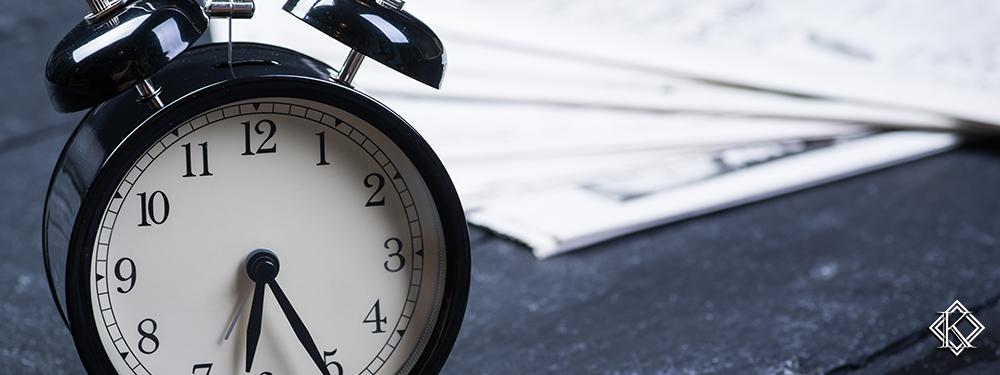 Uma mesa escura com alguns papéis e um relógio despertador, simbolizando o tempo que se precisa empenhar para providenciar as provas para aposentadoria especial